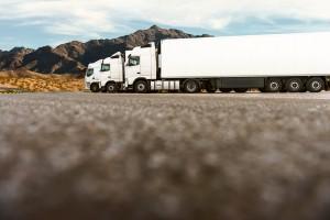 białe ciężarówki na tle gór